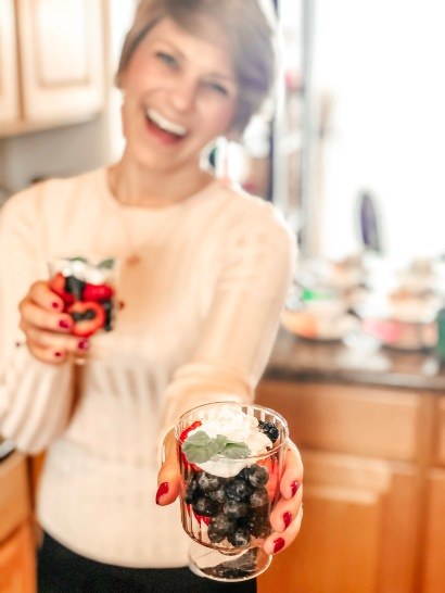 Nicole holding fruit parfaits up as she is faded in the background with focus on the fruit cup.