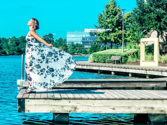 Nicole on a dock at Lake Woodlands staring out into the water with her dress fanned back.