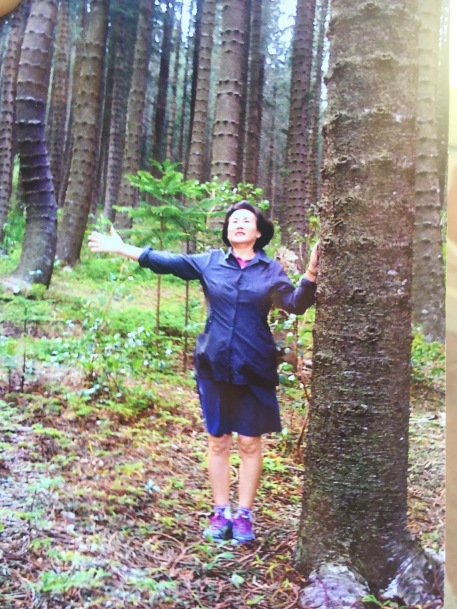 Ruby Kim taking a photo in a wooded area next to many large trees