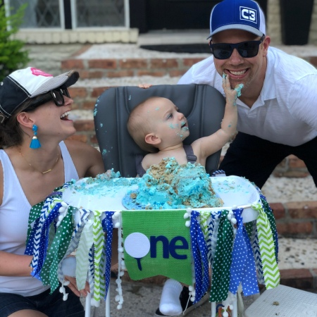 Wes and Nicole with Easton at his first birthday party while Easton puts cake on Wes' face